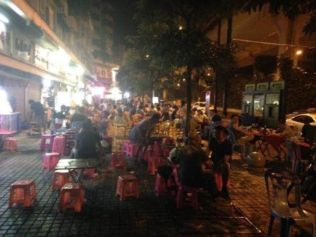 The bustling night time street scene on the terrace outside the hotel
