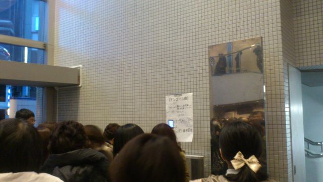 Japanese concertgoers queuing to photograph the hand written sheet of encores performed affixed to the wall in the entance of Omiya Concert Hall